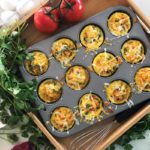 Mini muffin tin containing 12 egg muffins in a brown box, tomato and cilantro on side.