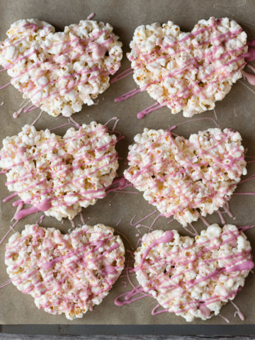 top down view of marshmallow popcorn hearts on a parchment-lined cookie sheet