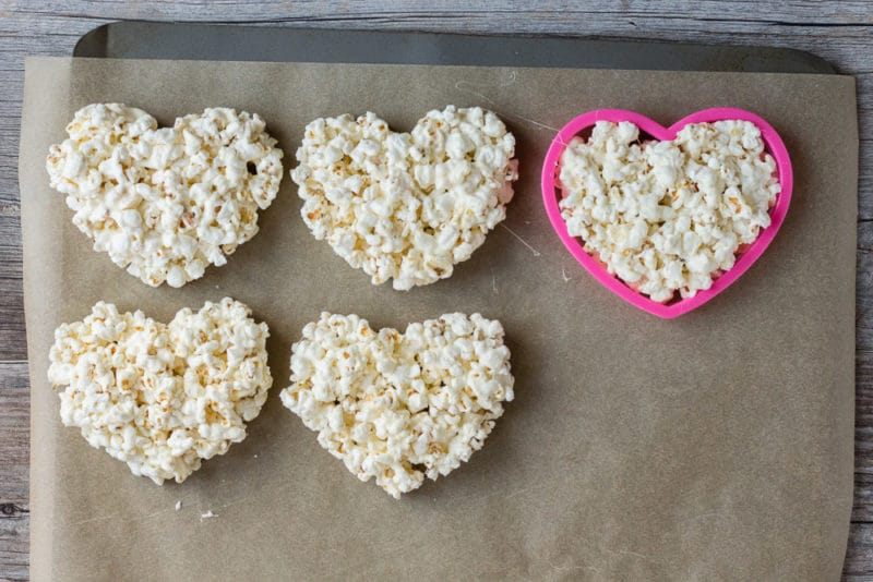 Marshmallow popcorn hearts being made on a parchment paper lined cookie sheet with a pink cookie cutter.