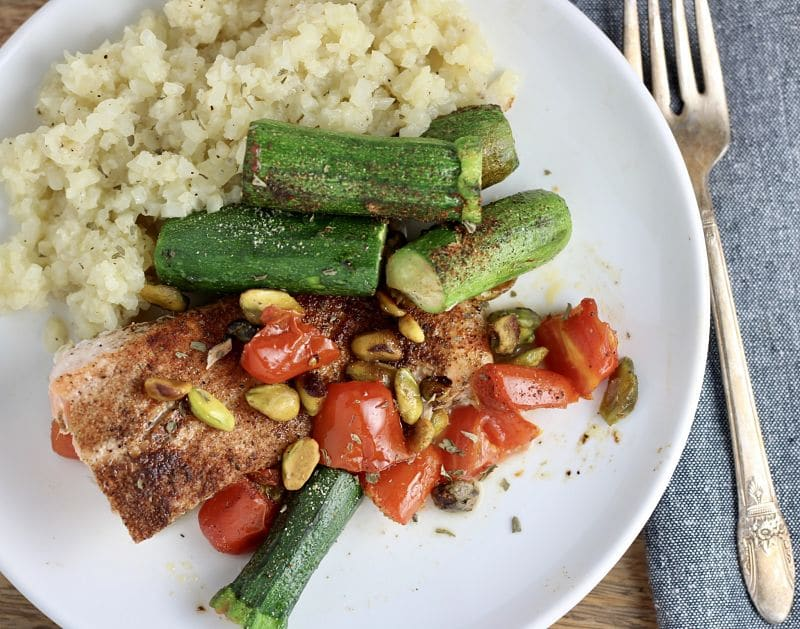 White plate containing a one pan pistachio salmon dinner with zucchini, tomatoes and a side of cauliflower rice.