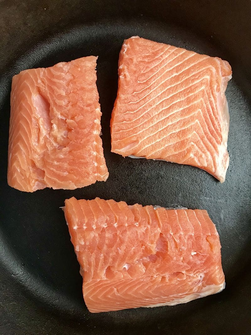 Salmon filets being pan seared in pan on stove top.