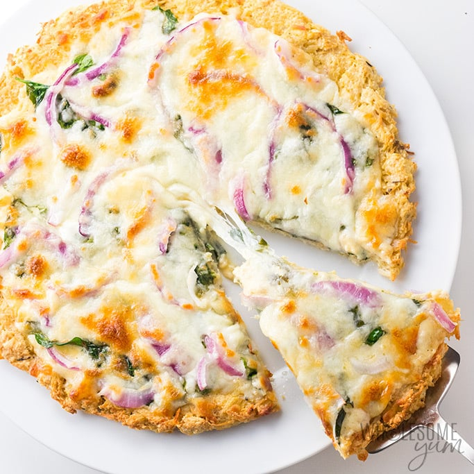 Keto Chicken Pizza Crust topped with an alfredo sauce, spinach and red onions on a white plate.