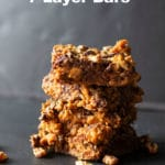A stack of three 7 layer bars on a black countertop.