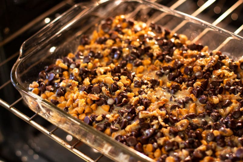 Glass pyrex dish containing layered ingredients to make 7 layer bars being cooked in the oven.