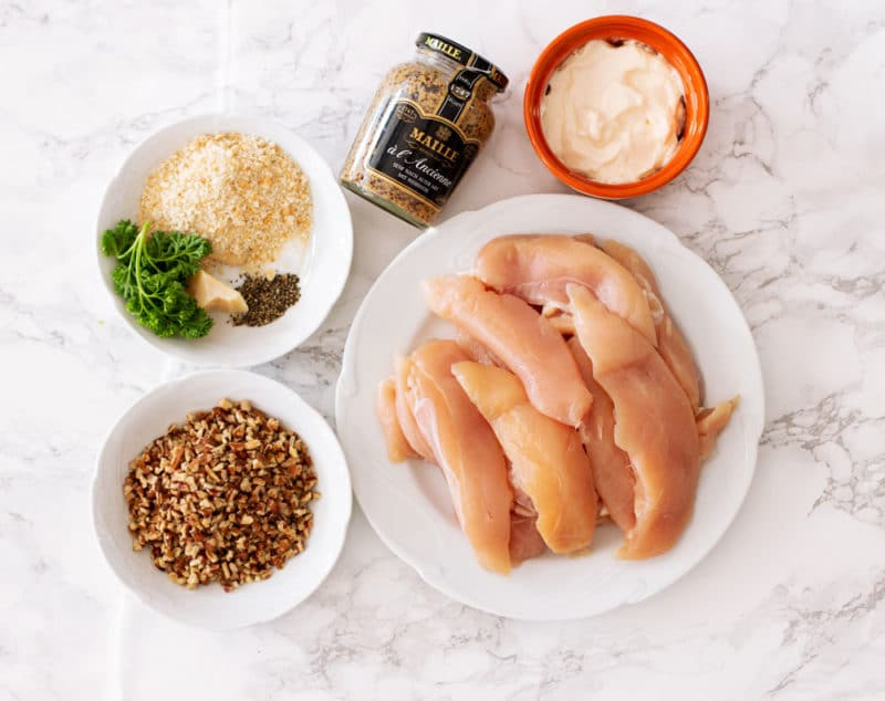 Ingredients to make Air Fryer Pecan Crusted Chicken Tenders, chicken tender breasts, pecan chips, mayonnaise, grain y dijon mustard, Parmesan cheese and parsley.