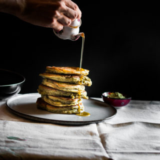 A photo of stacked matcha gluten free pancakes with lemon and maple sauce being poured over the top.
