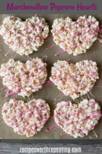 marshmallow popcorn hearts on a parchment-lined cookie sheet