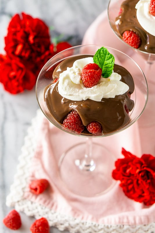 Two raspberry-mocha pudding parfaits on a pink napkin with red flowers and raspberries.