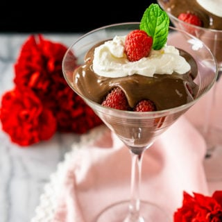A martini glass of raspberry-mocha pudding parfait with a black background.