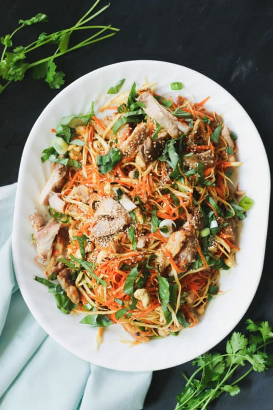 Paleo Asian chicken salad on a white plate topped with carrot spiralized zoodles and cilantro.