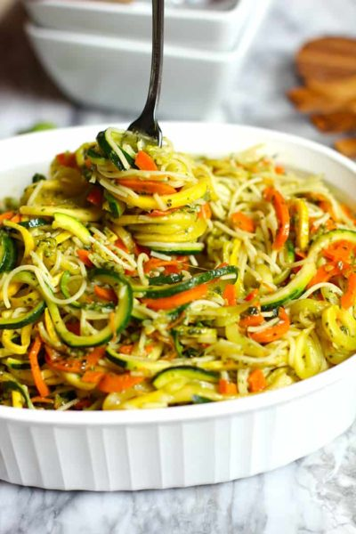 White bowl containing spiralizer vegetables of zucchini and squash zoodles with a light sauce, fork in zoodles.