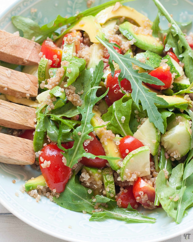 White bowl containing Quinoa and Avocado Salad with Balsamic Dressing, wooden salad tongs on side.