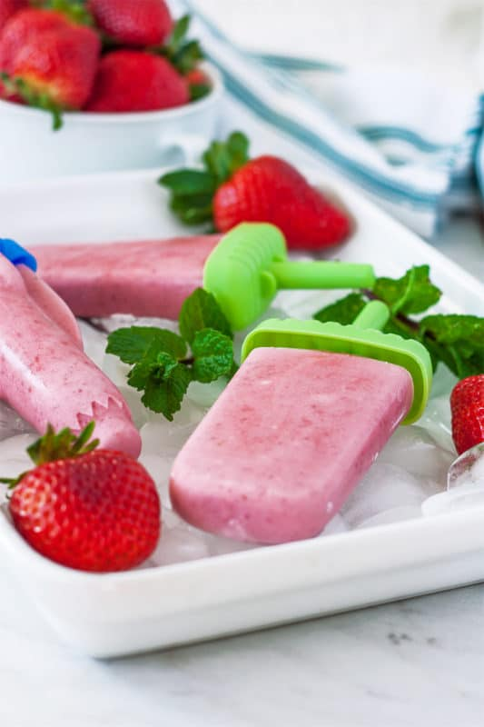 A side view of a strawberry popsicle recipe in a tray with ice.