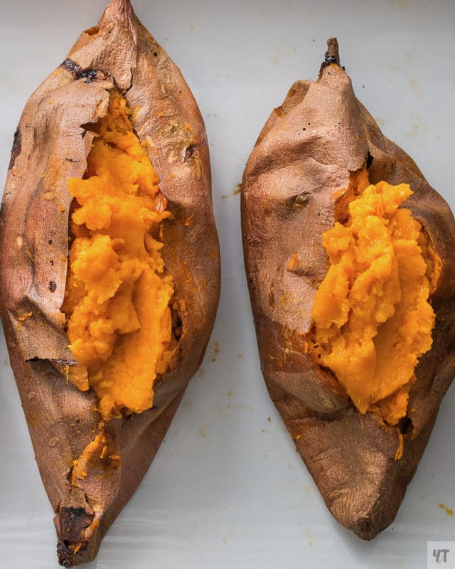 Two sweet potatoes on a white counter.