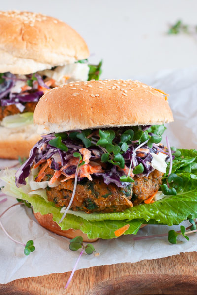 A gluten free and vegan Sweet Potato and Kale Patty on a gluten free bun with a lettuce and slaw topping.