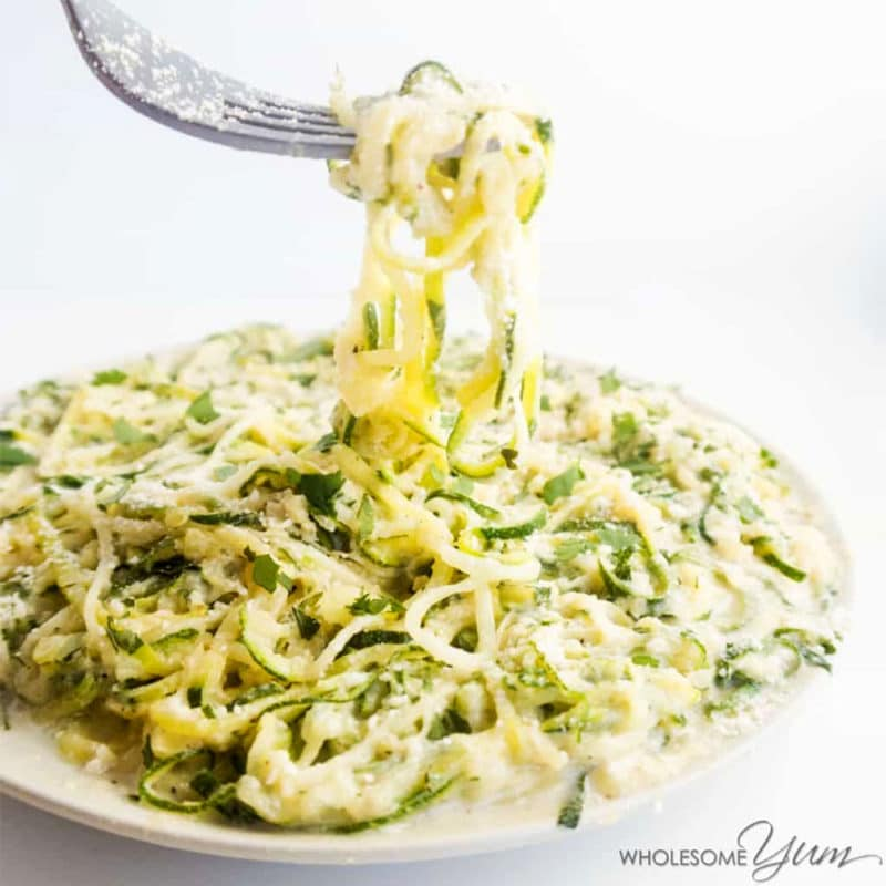 White plate containing a plate of alfredo zoodles, fork in zoodles topped with Parmesan cheese.