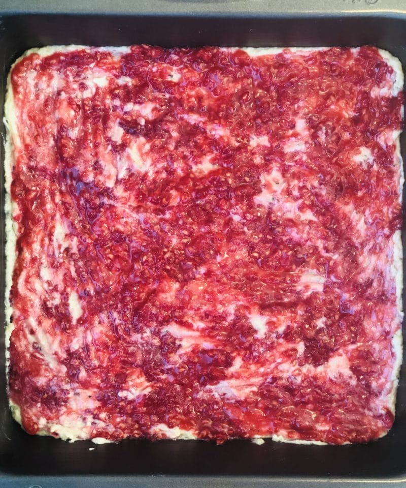 mashed raspberries spread over base layer of coconut raspberry bars (vegan)