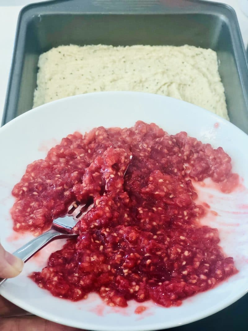 mashed raspberries on a white plate overlooking base bar layer in baking pan