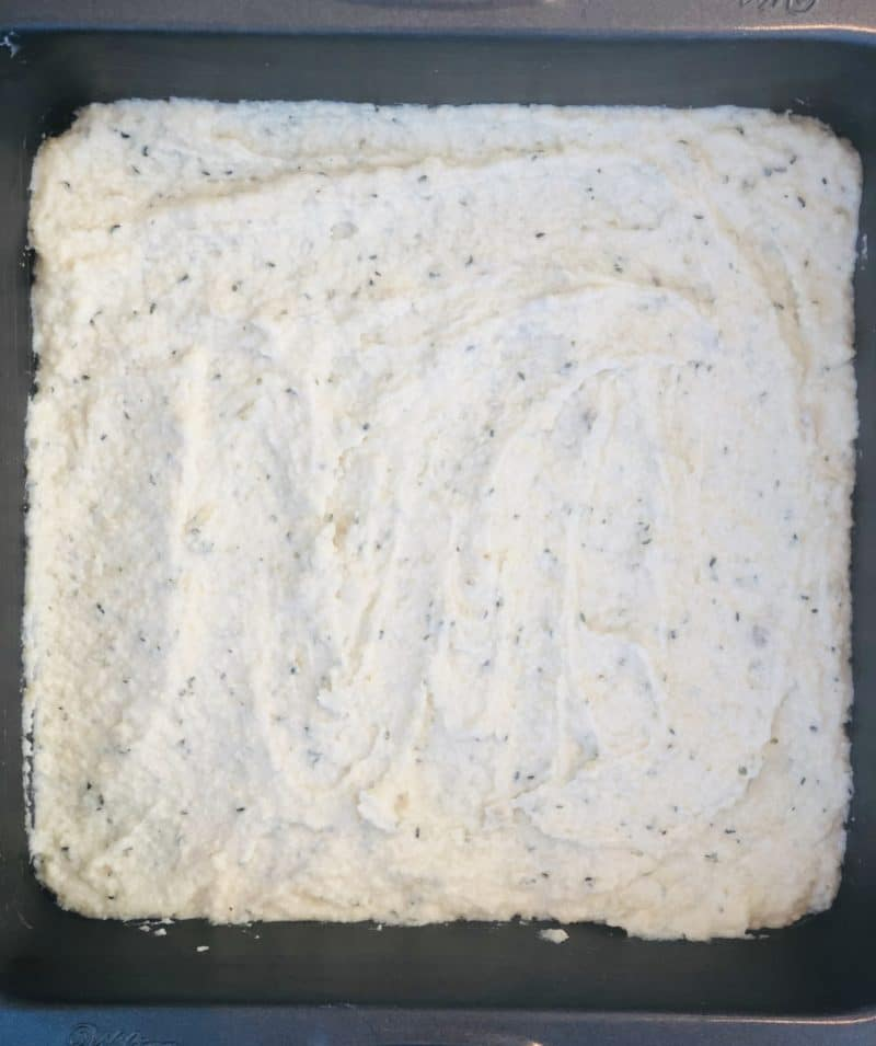 first layer of coconut raspberry bars (vegan) spread into a square pan