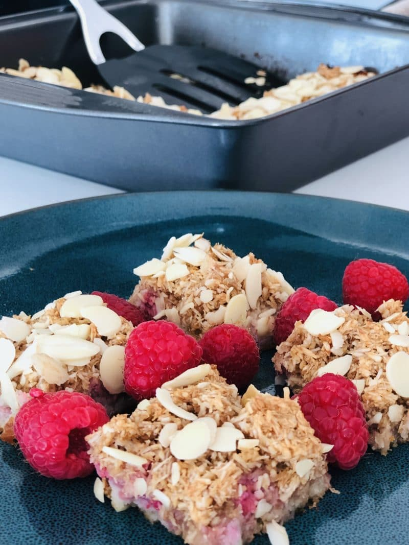 coconut raspberry bars and raspberries on a green plate with the pan in the background