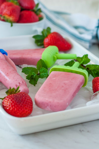 a side view of a strawberry popsicle recipe in a tray with ice