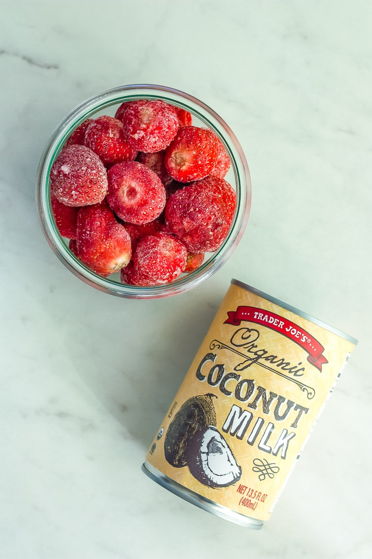 A bowl of frozen strawberries and a can of coconut milk on a white board.