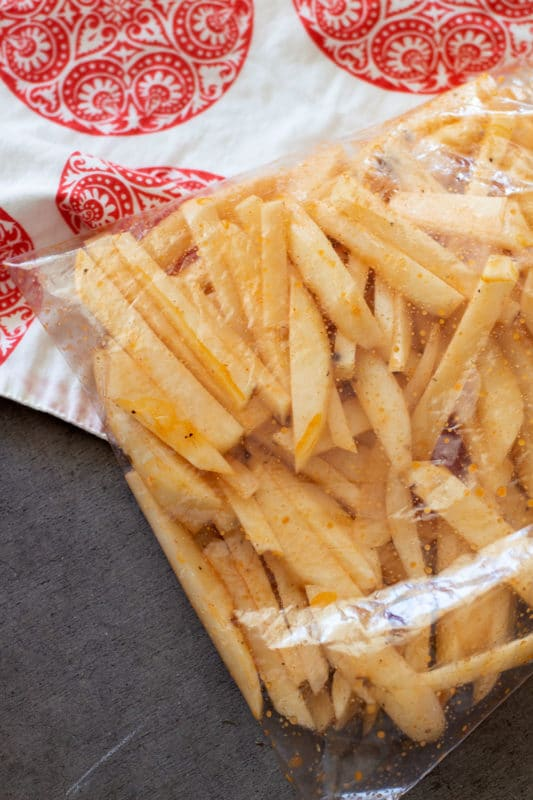 Ziplock bag filled with cut potatoes and seasonings to make air fryer french fries.