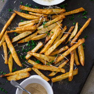 Air Fryer French Fries topped with Parmesan cheese and fresh parsley on a black cutting board.