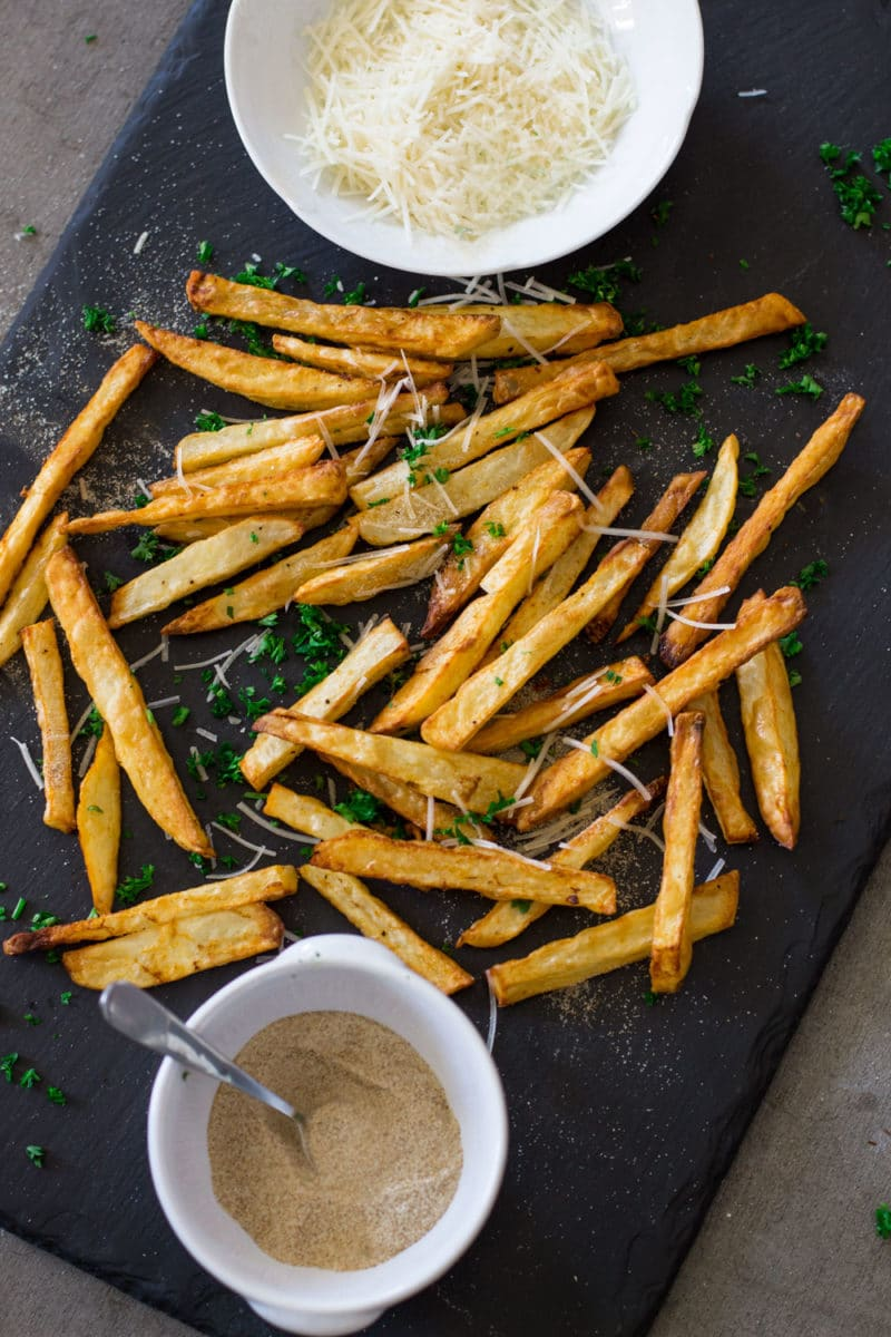 Black serving board containing air fryer french fries topped with Parmesan cheese and seasonings.