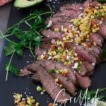 Sliced flank steak on a tray topped with forn salsa, avocado and lime on table.