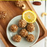 A plate of lemon bliss balls on a wooden board with lemon slices and dates.