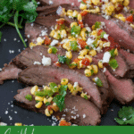 Close up of flank steak topped with corn salsa and cilantro.