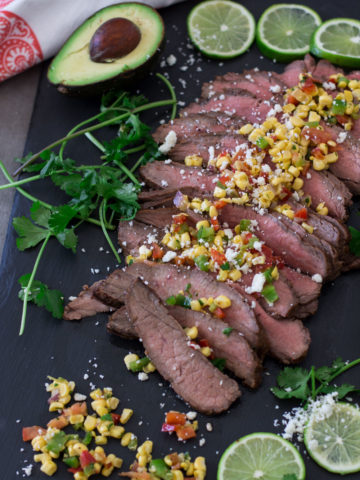 Sliced grilled flank steak on a black cutting board topped with a Mexican corn salad, avocado and lime on side.
