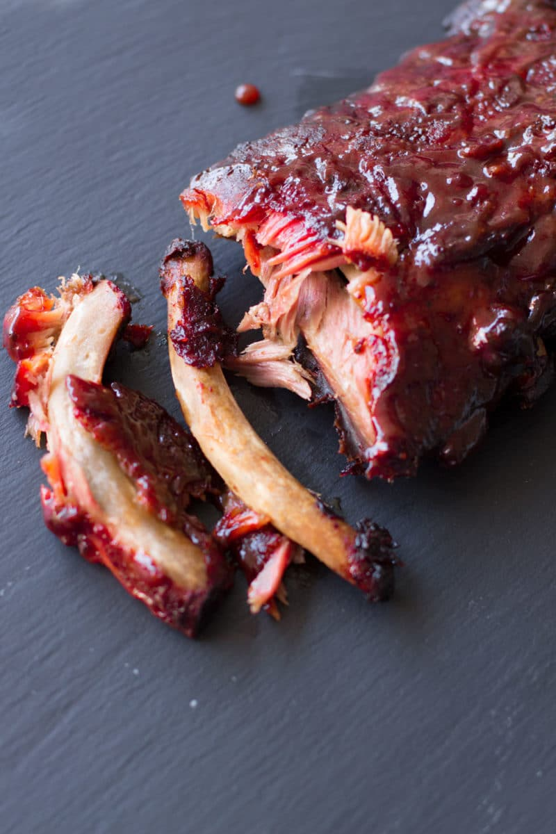 Slab of BBQ ribs on a black cutting board, meat falling off bone.