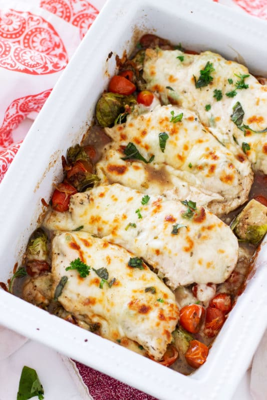 White pan containing One Pan Garlic Baked Chicken topped with melted mozzarella and fresh basil.