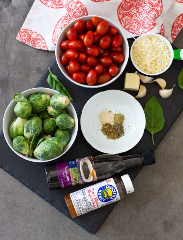 Black cutting board with cherry tomatoes, brussels sprouts, balsamic vinegar, honey and herbs.