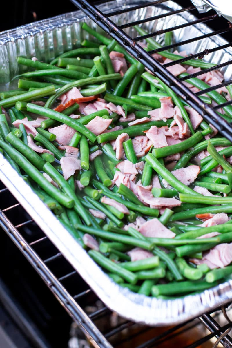 Aluminum pan containing green beans topped with bacon being placed in a smoker.