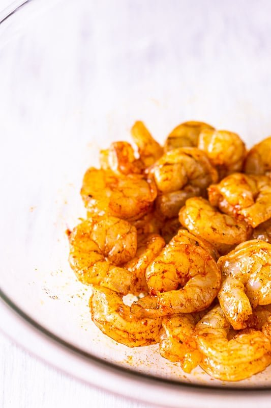 The raw shrimp in a glass bowl after they've been tossed with olive oil, salt, pepper and smoked paprika.