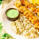 Two shrimp skewers on a bed of rice with a side of summer herb sauce.