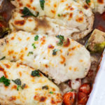 A close up of sliced chicken breasts topped with mozzarella and parsley.