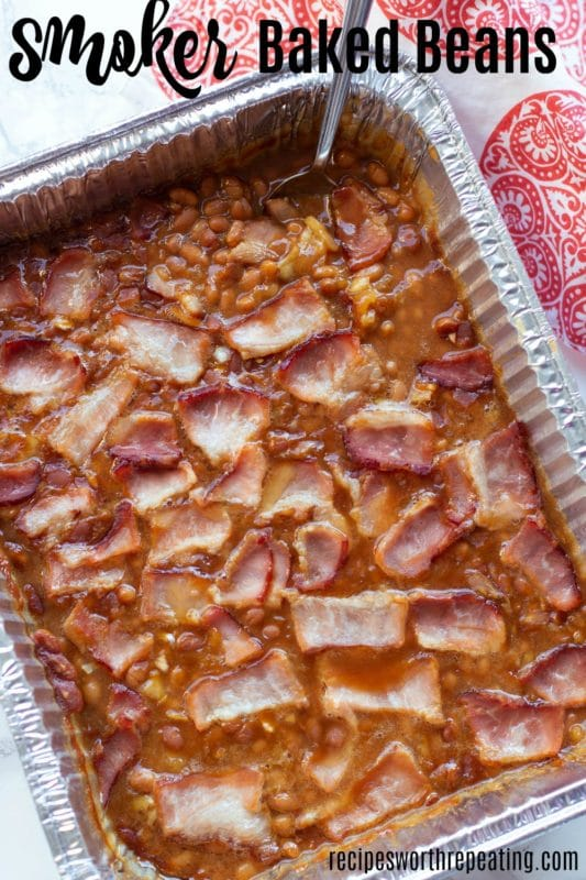 Pan containing baked beans cooked in a smoker topped with bacon.