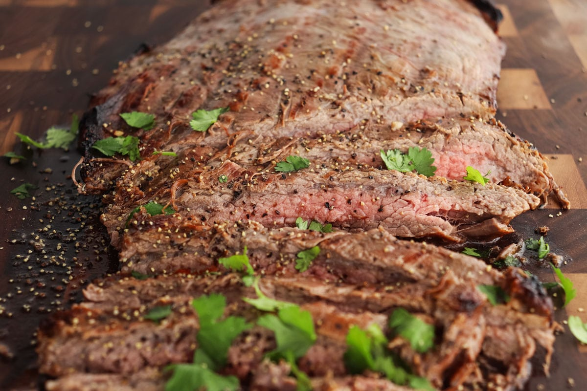 Sliced flank steak topped with fresh parsley.