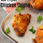 Baking pan containing crispy chicken thighs made in an air fryer, topped with parsley.