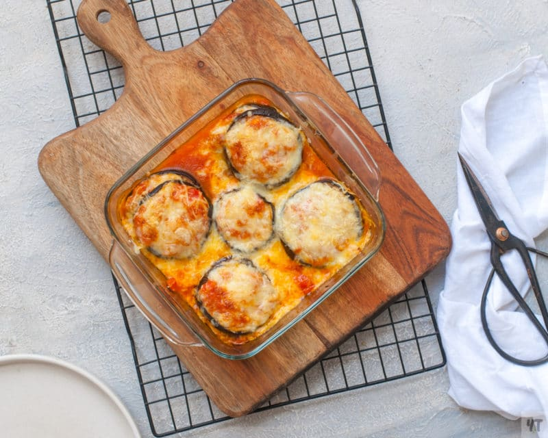 Baked eggplant topped with mozzarella and Parmesan cheese in a glass baking dish.
