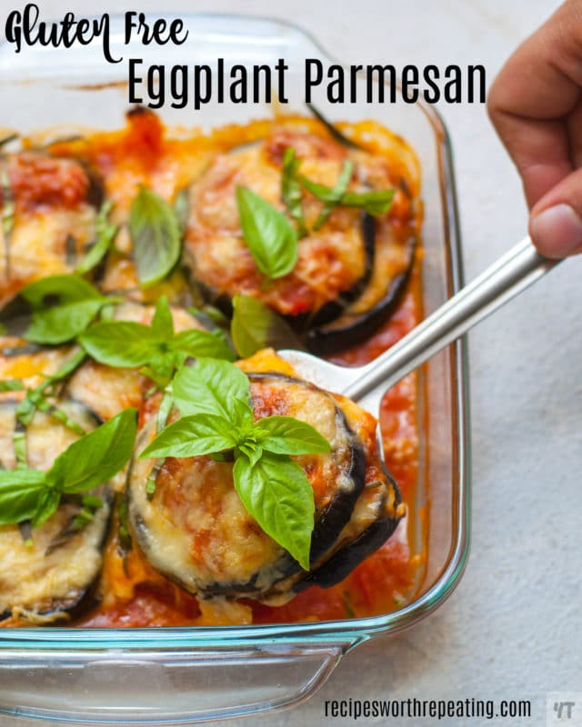 Glass baking dish containing a spoonful of eggplant parmesan topped with cheese and fresh basil.