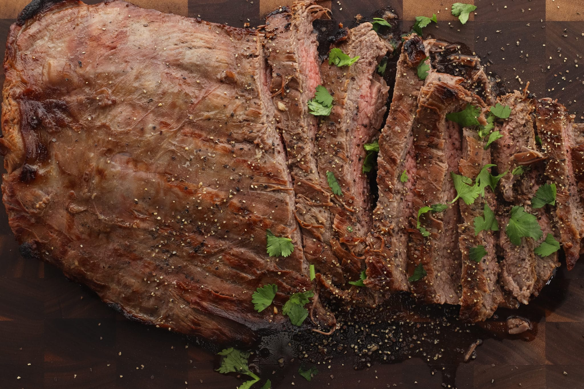 Flank steak on butcher block sliced and topped with fresh parsley.