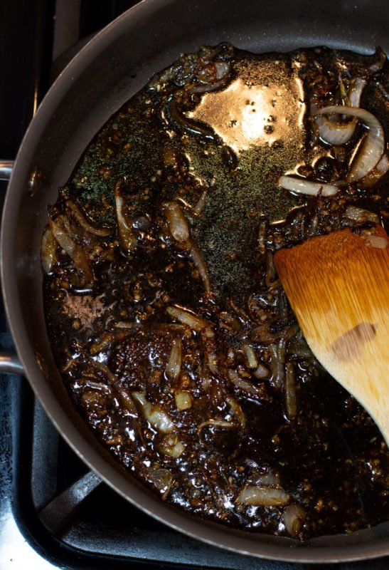Balsamic vinegar with onions and garlic sauteing in a skillet.