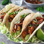 Spicy jackfruit tacos topped with lettuces and lime.