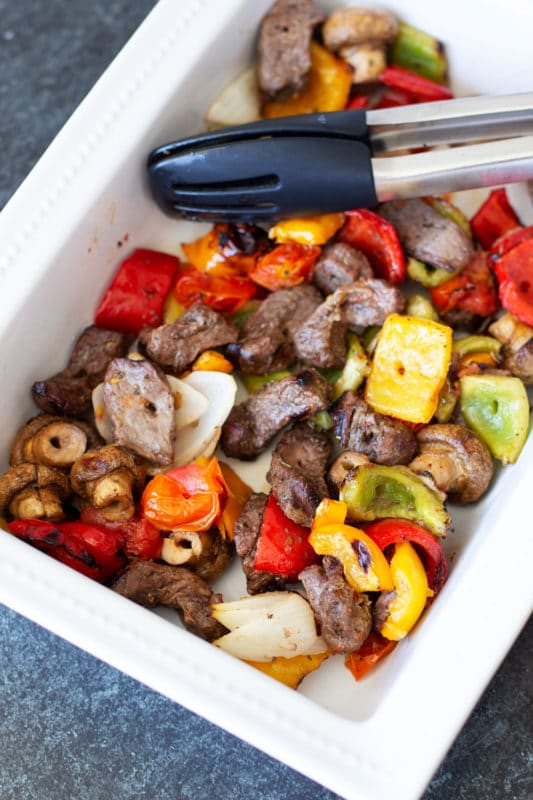 White dish containing steak and vegetable kebabs, tongs in dish.