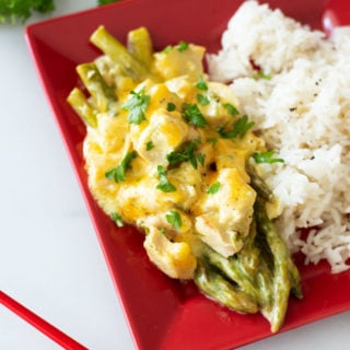 Red plate containing asparagus spears topped with melted sharp cheese and chicken, chopsticks in rice.